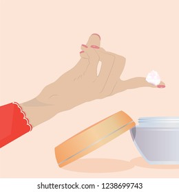 The woman's hand holds a skin cream from the  jar on her fingers