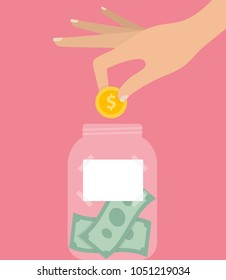 Woman's hand putting golden coin in to a jar filled with money and a white blank label on it. Savings and tipping concept