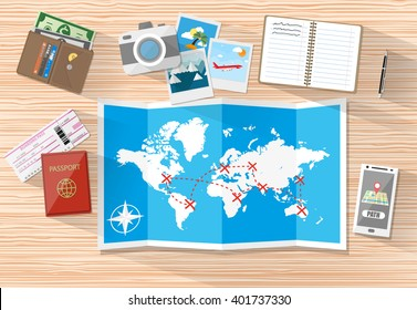 Wooden table with paper map of world and tourist equipment. passport, airplane ticket, notebook, smartphone with navigation application, photo camera photos, wallet. vector illustration in flat design