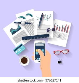 Work concept - business concept - flat design - top view - big ideas - bright ideas A human's hands holding a smart-phone that shown some business charts. Many objects (smart-phone, pens, papers...)