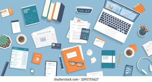 Workplace Desktop background. Top view of table, laptop, folder, documents, notepad, business card, purse, calendar, clock, books,coffee, passport, crumpled paper. Business background, organization.