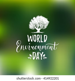 World environment day hand lettering card on blurred background. Vector tree illustration.