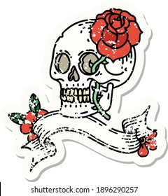 worn old sticker with banner of a skull and rose