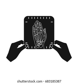 X-ray picture of the hand of a person in the hands of a radiologist. Medicine single icon in black style vector symbol stock illustration web.