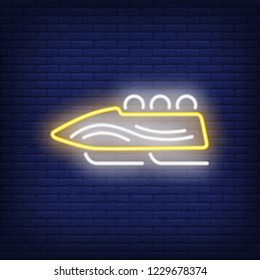 Yellow bobsleigh neon sign. Glowing bob with sport team on dark blue brick background. Can be used for sport, winter games, Olympic