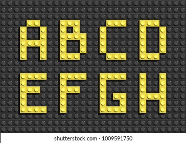 Yellow letters of alphabet from black building lego bricks background. lego bricks letters. lego alphabet