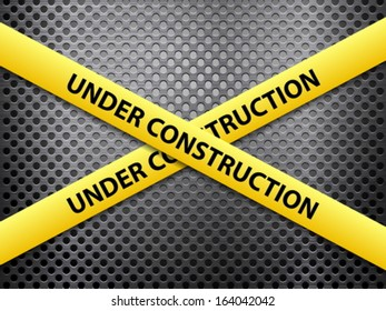 Yellow under construction tape on a metal background.