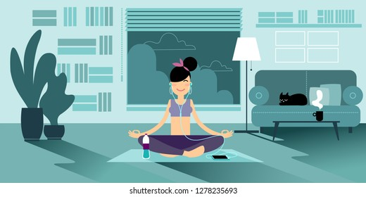 A Yoga girl in headphones meditates at home in the evening, sitting on a pilates mat in an easy sukhasana pose. Nearby there is a bottle of water, a cup of tea and a cat on the sofa.