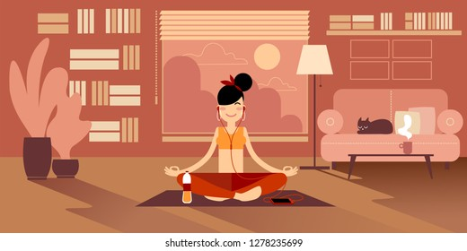 A Yoga girl in headphones meditates at home, sitting on a pilates mat in an easy sukhasana pose. Nearby there is a bottle of water, a cup of tea and a cat on the sofa.