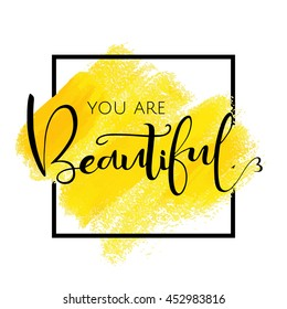 You are beautiful, inspirational phrase of black color in the frame. Yellow brush strokes with rough edges. Vector illustration. Hand drawn element for your design.