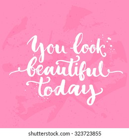 You look beautiful today. Inspirational quote, white brush calligraphy handwritten on pink background. Vector lettering for card and poster design, social media content and fashion.