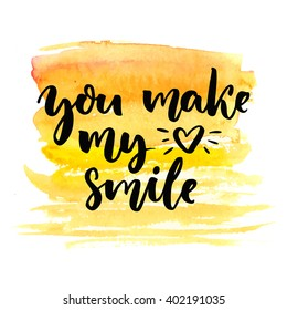 You make my heart smile. Brush calligraphy on yellow watercolor texture. Postcard with lettering about love.