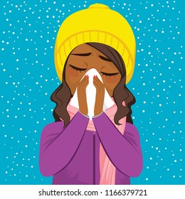 Young African American woman having flu blowing nose with white paper tissue on winter