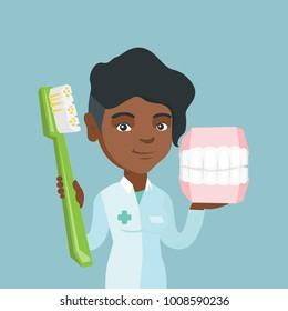 Young african-american dentist holding a dental jaw model and a toothbrush in hands. Dentistry, dental care, tooth care concept. Vector cartoon illustration. Square layout.