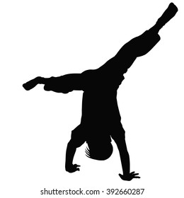 A young boy stands on his hands outstretched to the side legs