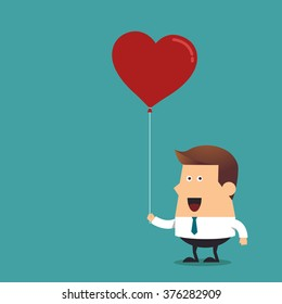 Young businessman holding red heart shaped balloon