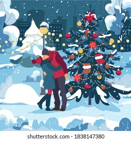 Young couple kiss, enjoying, dressed warm. Woman with a man in the evening walking under falling snow in the city park by the christmas tree. Vacation together in winter holidays.
