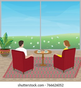 The young couple  sit in the armchairs and looking out the window on the green field with the daffodils