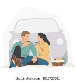 A young couple sits on the background of the car and looks at each other. They hold cups of tea in their hands. There is a basket with foods near. Autumn vibes and colors. Picnic outdoors.