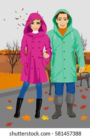 young couple wearing raincoats standing in park in autumn