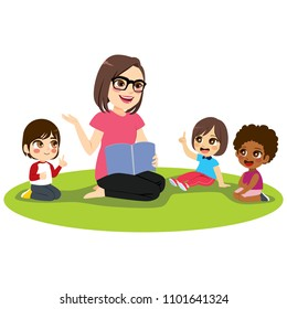 Young female kindergarten teacher explaining lesson reading book to attentive kids sitting on floor