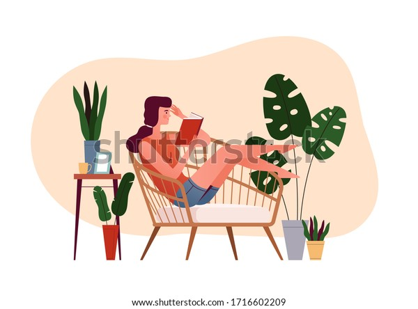 Young girl sits in an armchair and reads a book. The concept of a cozy reading at home. Home daily activities