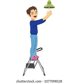 Young happy man changing light bulb with ladder