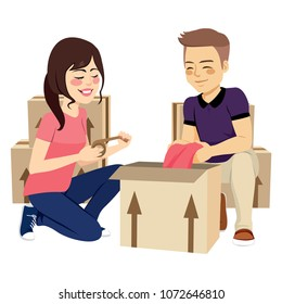 Young lovely couple packing things in box moving concept