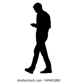 Young man going forward and holding a cell phone and writing sms, vector silhouette