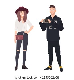 Young man holding camera and making photo of his girlfriend. Fashionable romantic couple. Funny cute male and female cartoon characters isolated on white background. Flat vector illustration.