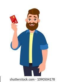 Young man is holding credit/ debit card.  Man is showing banking card.