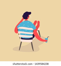 The young man resting while sitting on a chaise lounge, drinking water and talking on the phone. The young man vacationing in beach clothes. The man is working on the phone while on vacation.