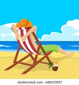 Young man in straw hat sitting in deck chair on tropical beach looks into the distance