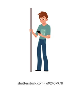 Young man, student, teenager travelling by subway, standing, holding handrail, using phone, cartoon vector illustration isolated on white background. Full length portrait of young man in subway, bus