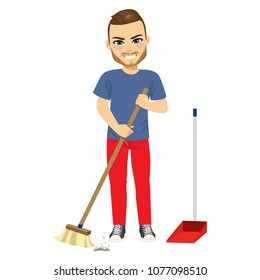 Young man sweeping home with broom doing household chores