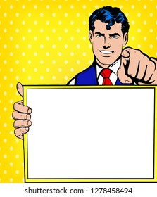 Young Smiling Business man pointing finger at you and holding empty, blank white borad, sign or paper sheet. Vector illustration in Comic Book Pop Art retro vintage style