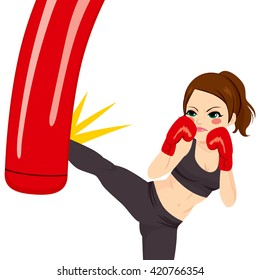 Young strong woman kicking red punching bag with powerful leg kick