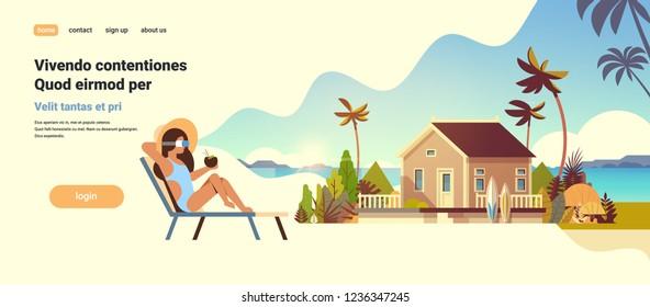 young woman bikini wear digital glasses sitting sun lounger virtual reality vision villa house tropical beach summer vacation concept flat copy space
