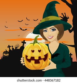 Young woman dressed like witch wearing dark clothing and holding pumpkin in hand