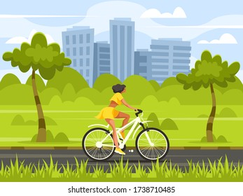 Young woman rides a bicycle in a city park on the background of the metropolis