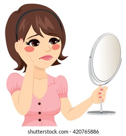 Young woman with sad expression looking herself in a mirror unhappy