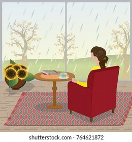 A young woman sits in her armchair and looks out the window as the rain falls