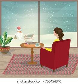 A young woman is sitting in her armchair looking out of the window as snow falls
