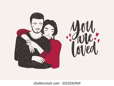 Young woman standing behind man and warmly embracing him and You Are Loved hand lettering decorated with tiny hearts. Loving romantic couple. Vector illustration for Valentine's day greeting card.