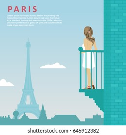 Young woman stands on balcony looking at Eiffel Tower in Paris