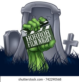 A zombie or Halloween monster hand coming out of a grave holding a movie clapper board. Reading horror film night advertising a scary cinema event or festival screening