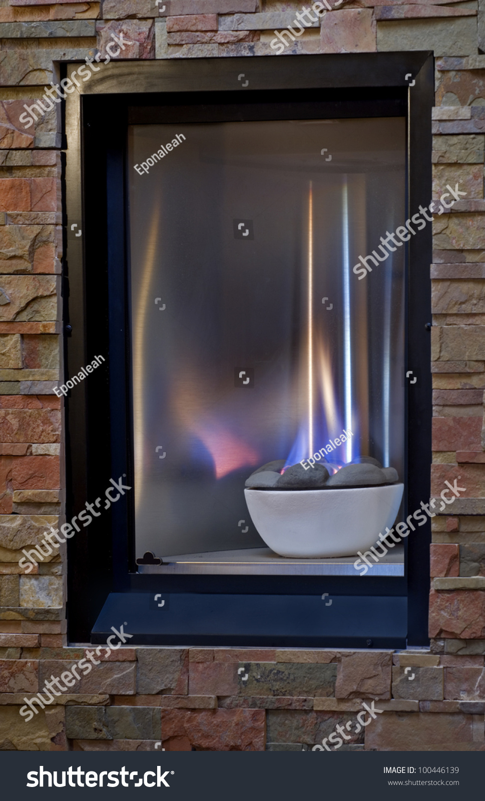 A Cozy Gas Fireplace With Blue And Yellow Flames Set Into A Warm Flagstone Wall Stock Photo