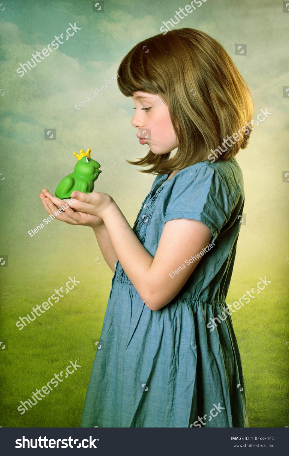 little girl kissing frog prince stock photo 100583440