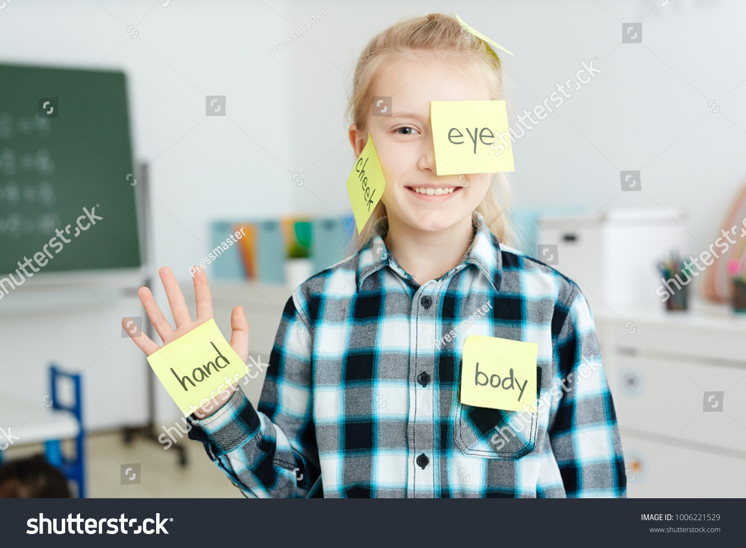 Happy schoolgirl having sticky notepapers with English names of body parts on her hand, cheek and eye #1006221529