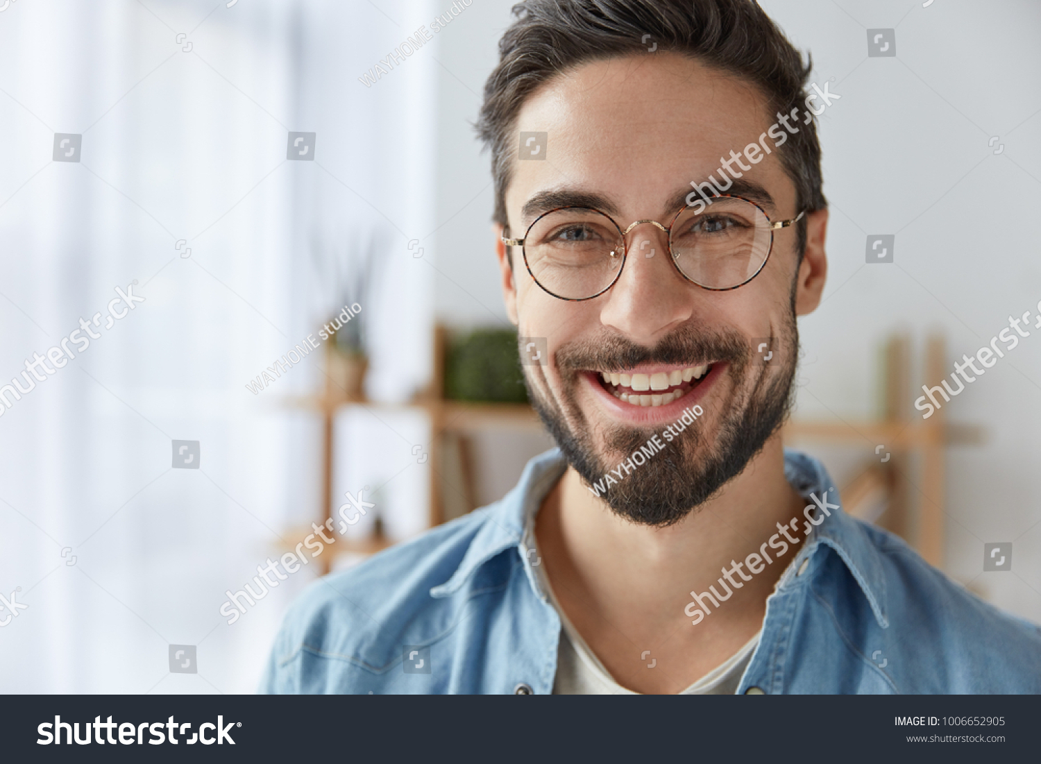 Close up shot of cheerful satisfied attractive male with stubble, has broad smile, wears round spectacles, rejoices success at work, stands against cozy interior. Fashionable designer glad be praised #1006652905 - 123PhotoFree.com